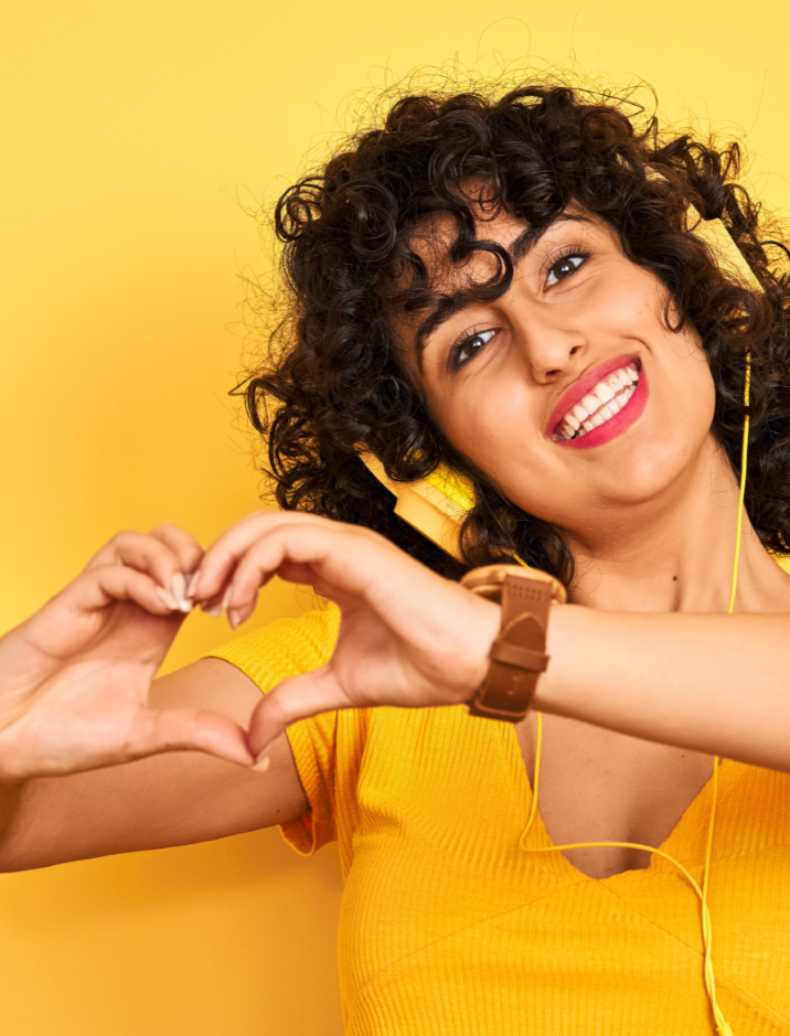 Smiling girl with headphones doing heart hands
